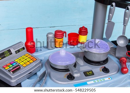 Set of plastic kitchen toy and blue painted on wooden background