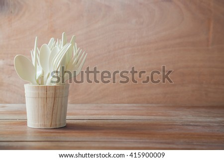 Set of plastic spoons on wood table