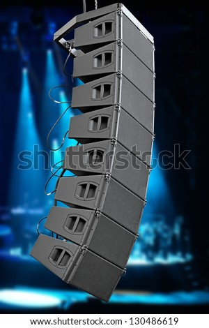 set of powerful speakers with blue light and stage in background - stock photo