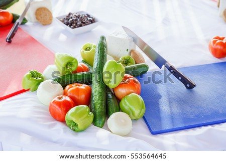 set of products for a Greek salad on the table with knife and cutting board.