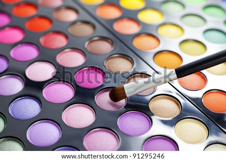 Set of professional colorful eyeshadow palette in close-up view with a brush.