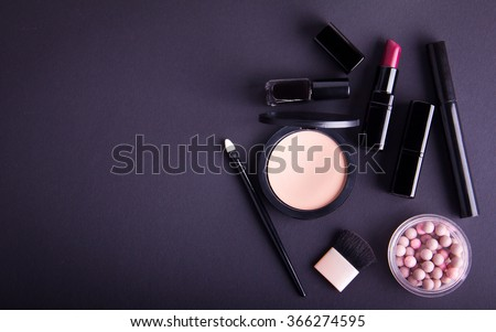 Set of professional cosmetic: make-up brushes, shadows, lipstick, nail polishes on black background. Overhead view. Place for your text. Vignetted. - stock photo