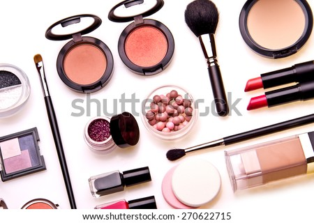 Set of professional cosmetic: make-up brushes, shadows, lipstick, nail polishes - partly isolated with shadows on white background. Overhead view.