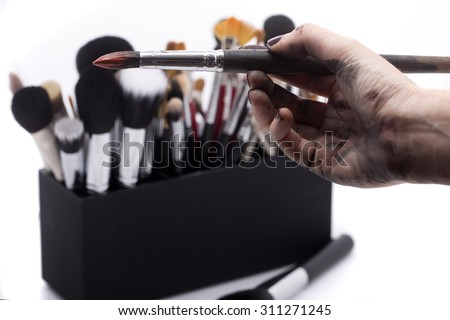 Set of professional make-up brushes for eyeshadow powder and facial foundation for visagistes in black plastic box and human hand holding one brush on white background, horizontal picture - stock photo