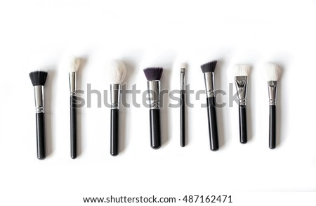 Set of professional make up brushes of different sizes and shapes isolated on white top view.