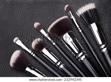 Set of professional makeup brushes over black leather background - stock photo