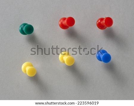 Set of push pins in different colors, with real shadows, isolated on gray background. - stock photo