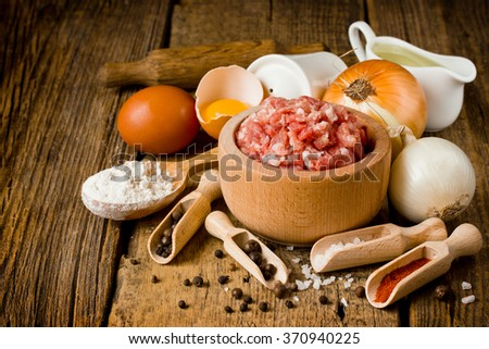 Set of raw ingredients for making meat dumplings: mince, onion, egg, oil, spices, flour on a wooden table. Russian traditional pelmeni cooking process - stock photo