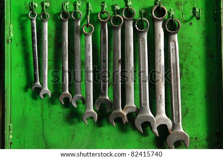 set of real used stainless spanners on green wall - stock photo