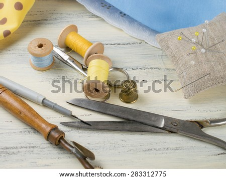 Set of reel of thread, centimeter, fabric, thimble and scissors, seam ripper, toothed wheel, needle and pins for sewing and needlework on the wooden board in Shabby Chic style.   - stock photo