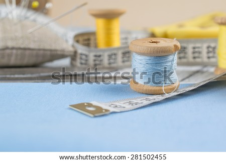 Set of reel of thread, scissors, centimeter, fabric, needle and pins for sewing and needlework. Still life photo with tools for handmade. - stock photo