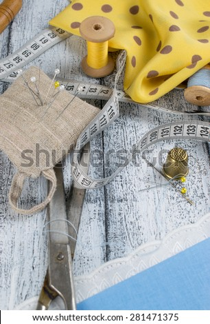 Set of reel of thread, scissors, centimeter, thimble, fabric, needle and pins for sewing and needlework in Shabby Chic style. Still life photo with tools for handmade. - stock photo