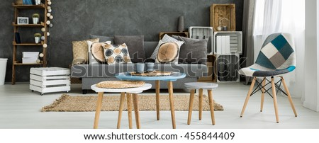 Set of round coffee tables with straw mats in a creatively furnished studio flat
