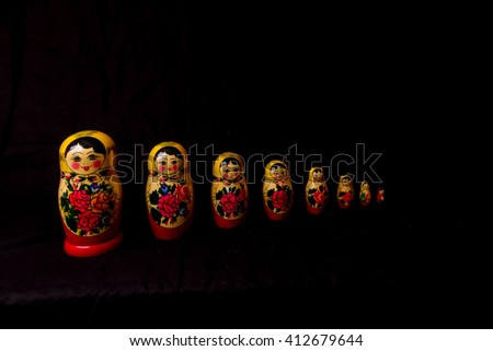 Set of Russian Dolls matryoshka in row, on black background.