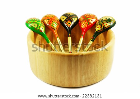 Set of russian wooden spoons on wooden bowl isolated on white - stock photo