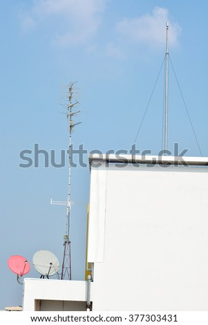 set of satellite dish and TV antennas on the house roof communication technology network on building under blue sky