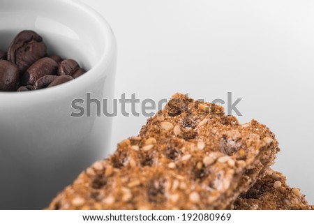 Set of saucers full coffee beans with crispbread on white background - stock photo