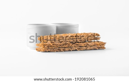 Set of saucers with crispbread on white background - stock photo