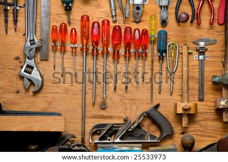 set of screwdrivers and other tools hanging in wooden cupboard against a wall - stock photo