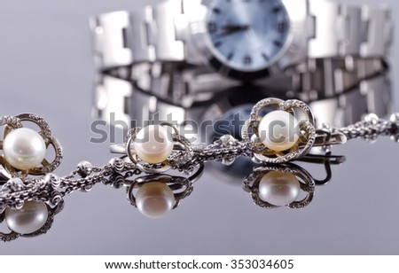 set of silver jewelry with pearls : an elegant ring and earrings in the shape of leaves - stock photo