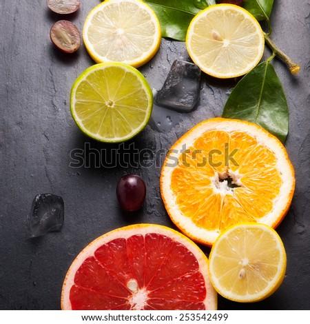 Set of sliced citrus fruits lemon, lime, orange, grapefruit with ice over stone black background. Top view. - stock photo