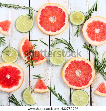 Set of sliced citrus lemon, lime, grapefruit, mint and rosemary on wooden background. View from above. - stock photo