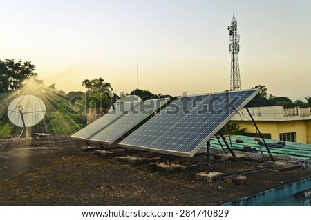 Set of small solar panels on the roof along with dish antenna and mobile phone tower at the background - stock photo