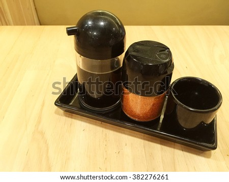 Set of soy sauce bottles on wooden table background - stock photo