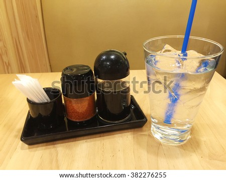 Set of soy sauce bottles with a glass of water on wooden table background - stock photo
