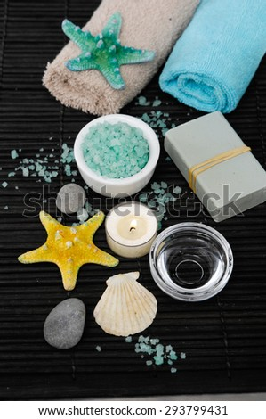 Set of spa stones with shell, soap, towel, candle on bamboo mat - stock photo