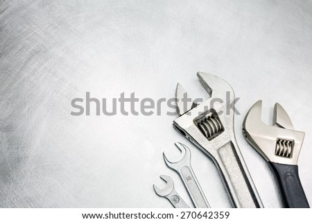 Set of spanners and wrenches on scratched metal background - stock photo