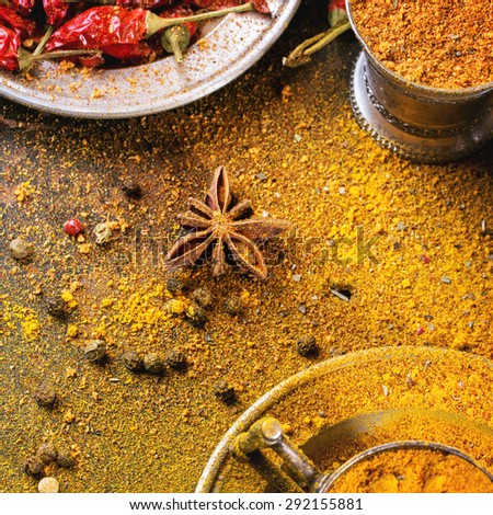 Set of spices pepper, turmeric, anise, coriander in vintage metal cups over yellow curry powder. Top view. Square image - stock photo