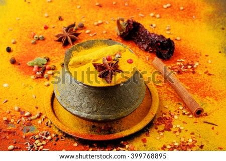 Set of spices pepper, turmeric, anise, dry chili in vintage metal cups over yellow curry powder. Food or spicy cooking concept, Healthy eating Background. - stock photo
