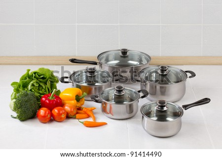 Set of stainless pots and pan with glass lids - stock photo