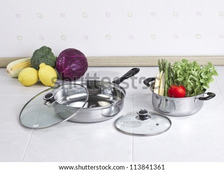 Set of stainless pots with glass lids and vegetables - stock photo