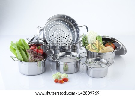 Set of stainless pots with lids and vegetable - stock photo