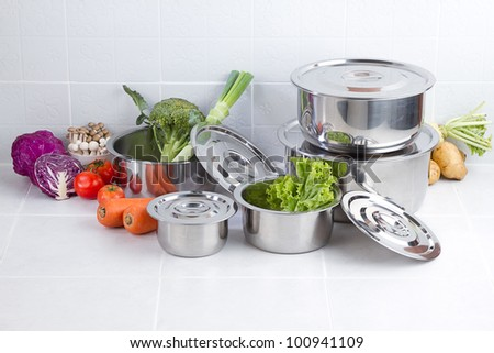 Set of stainless pots with lids and vegetables - stock photo