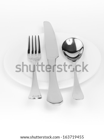 set of stainless steel spoon, fork, knife on small white plate on white background - stock photo