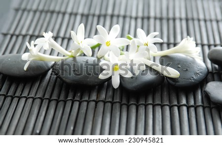 Set of stones with white flower on bamboo mat - stock photo