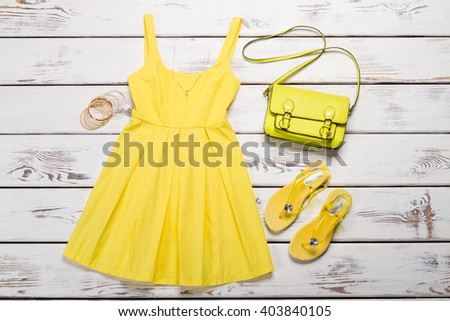 Set of summer clothes. Yellow dress with a handbag, sandals and accessories. - stock photo