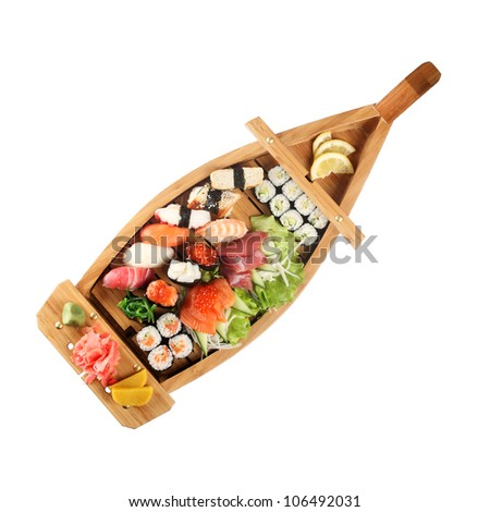 Set of sushi on wooden stand in the form of the boat isolated on white - stock photo