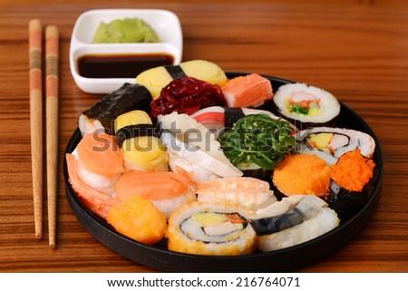 Set of Sushi Roll and Sashimi Japanese food on wooden tray  - stock photo