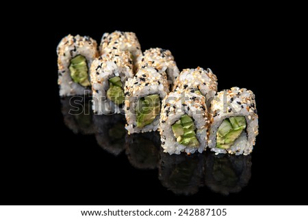 set of sushi rolls with cucumber on a black background - stock photo