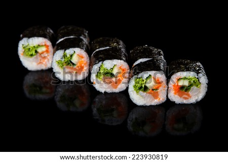 set of sushi rolls with salmon on a black background - stock photo