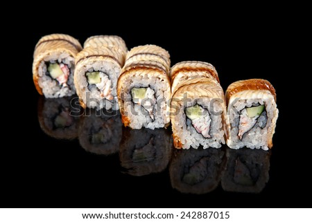 set of sushi rolls wrapped in eel on a black background - stock photo