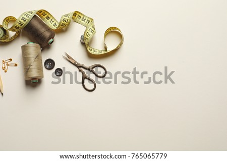 Set of tailoring tools and accessories on table, top view