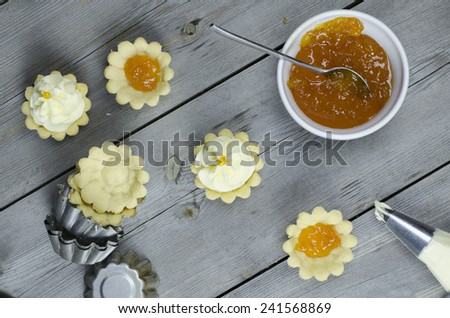 set of tasty tartlets with apricot jam and whipped cream - stock photo