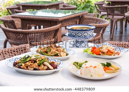 Set of Thai food such as fried rice fried cashew nut vegetable and salad on table.