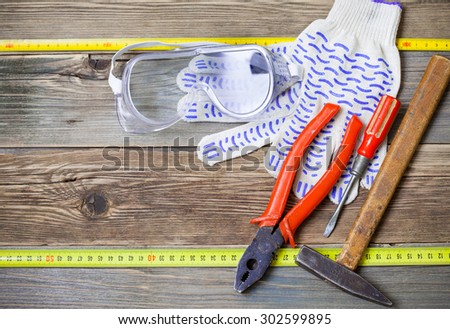 set of the old locksmith tools, safety glasses and work gloves on the vintage workbench - stock photo
