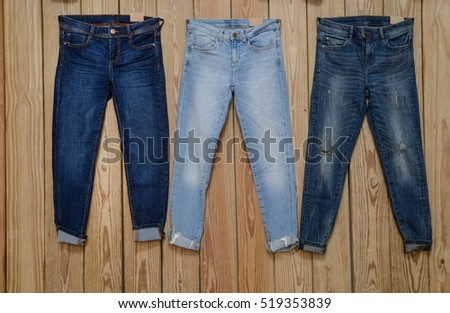 Set of three Blue Jeans- wooden background